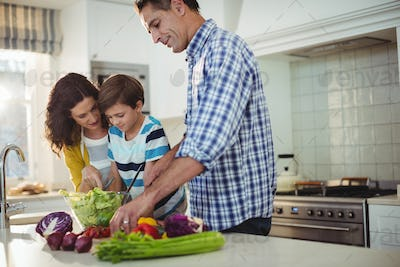 Parents and son preparing salad in the kitchen