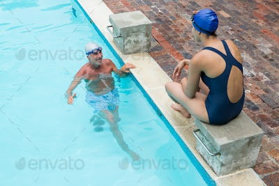 Senior man interacting with woman at poolside