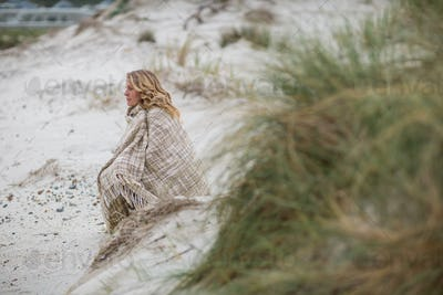 Mature woman wrapped in shawl on the beach