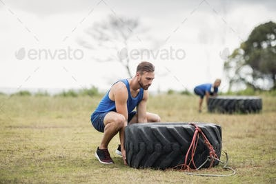 Fit woman flipping a tire during obstacle course