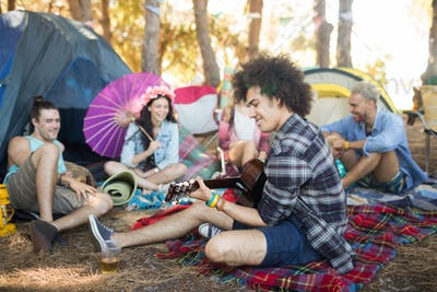 Young man playing guitar while sitting with friends at campsite