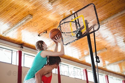 Man assisting female friend while playing basketball