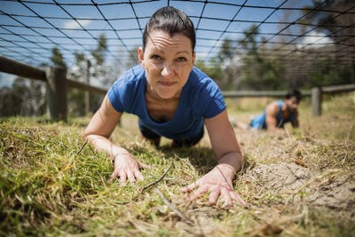 Fit woman crawling under the net during obstacle course