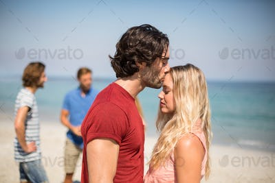 Man kissing girlfriend on forehead against friends at beach