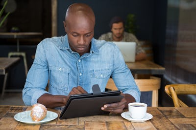 Man using tablet computer at table in coffee shop
