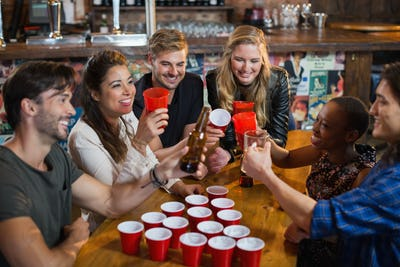 Happy friends drinking beer while sitting around disposable cups in bar