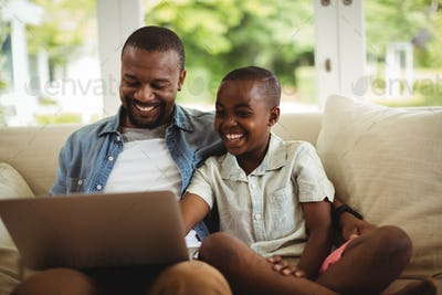 Father and son using laptop in living room