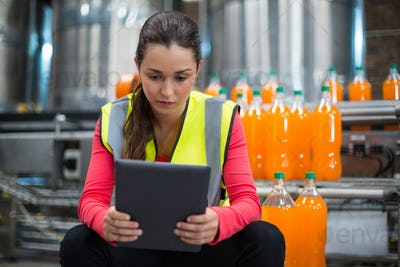 Female factory worker using digital tablet