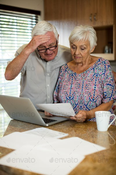Senior couple calculating their invoices with laptop in the kitchen