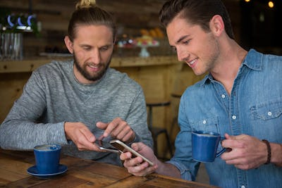 Happy male friends using smart phone in coffee house