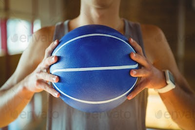 Midsection of basketball player holding ball