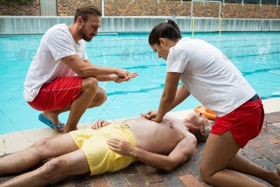 Lifeguards pressing chest of unconscious senior man