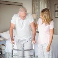 Senior woman helping man to walk with walker