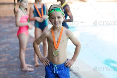 Happy little boy wearing medal at poolside