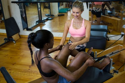 Smiling trainer assisting woman with pilates on reformer