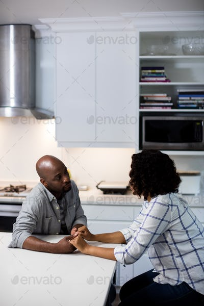Couple sitting at table and holding hands in kitchen