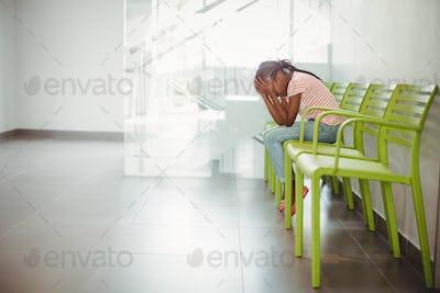 Upset girl sitting on chair in corridor