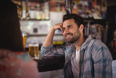 Happy couple interacting while having beer at counter