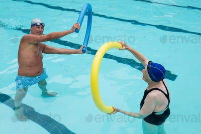 Senior couple exercising with pool noodle