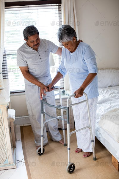 Senior man helping senior woman to walk with walker