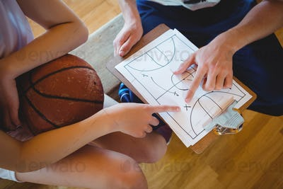 Close up of coach explaining diagram to female basketball player
