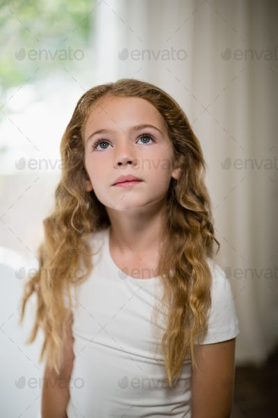 Close-up of thoughtful girl looking up