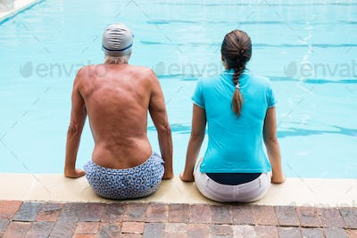 Female coach and senior man sitting at poolside