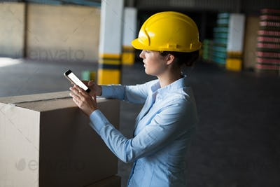 Female factory worker using mobile phone