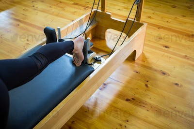 Woman practicing stretching exercise on reformer