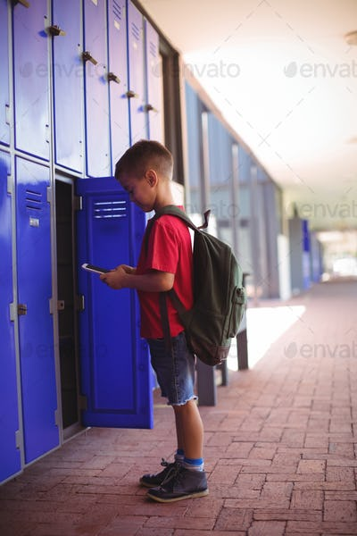 Side view of boy using mobile phone by open locker