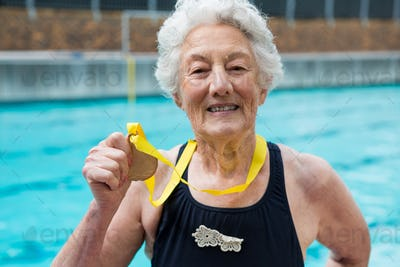 Senior woman showing gold medal at poolside