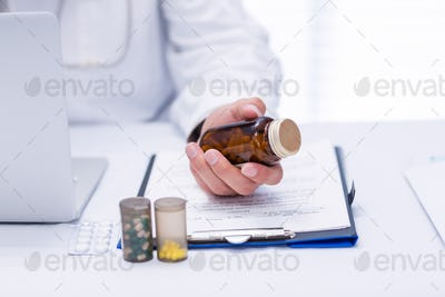 Mid section of male doctor checking medicine