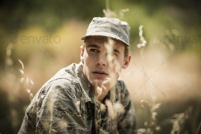 Thoughtful military soldier relaxing in grass