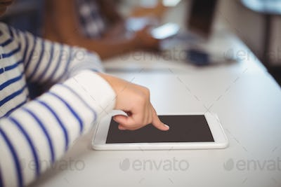 Students using digital tablet and laptop in classroom