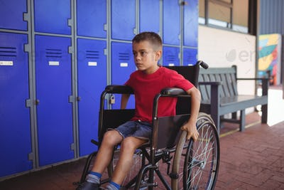 Thoughtful boy sitting on wheelchair