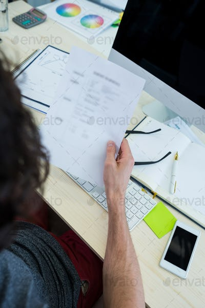 Business executive holding document at his desk