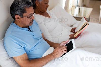 Senior woman reading a novel and senior man using digital tablet on bed