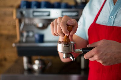Barista using tamper to press ground coffee into portafilter in cafe