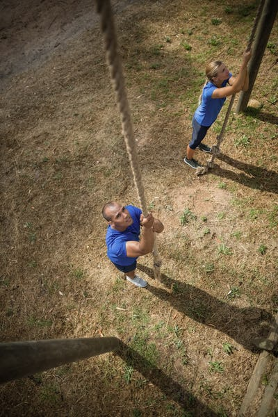 Fit person climbing down the rope during obstacle course