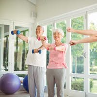 Female trainer assisting senior couple in performing exercise