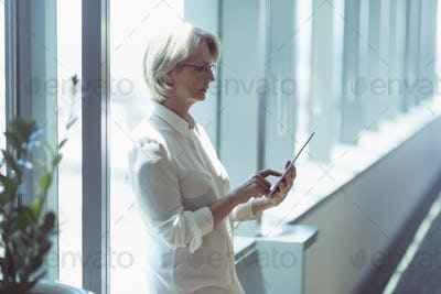 Businesswoman woman using tablet computer by window