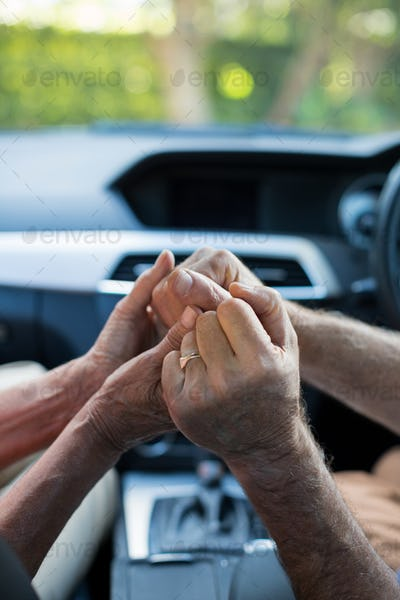 Senior couple holding hands in car