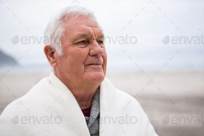Senior man wrapped in shawl on beach