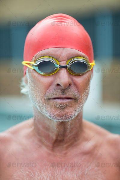 Shirtless senior swimmer wearing goggles
