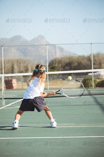 Rear view of girl playing tennis