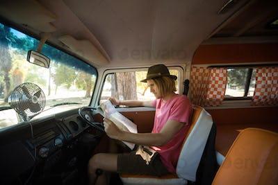 Side view of man reading map in camper van