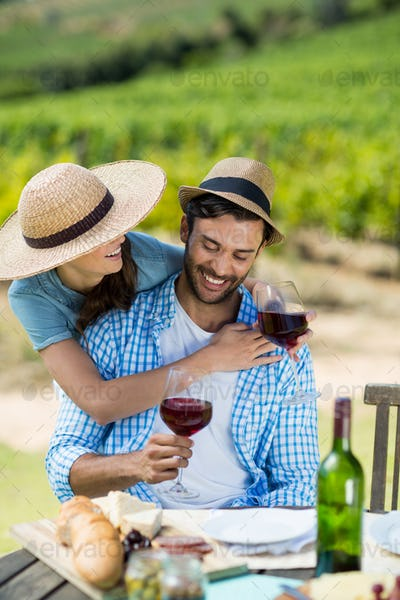 Happy couple holding red wine glasses at table