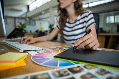 Mid section of female graphic designer using graphics tablet at desk