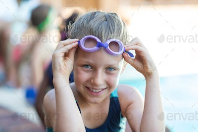 Smiling little girl holding swimming goggles