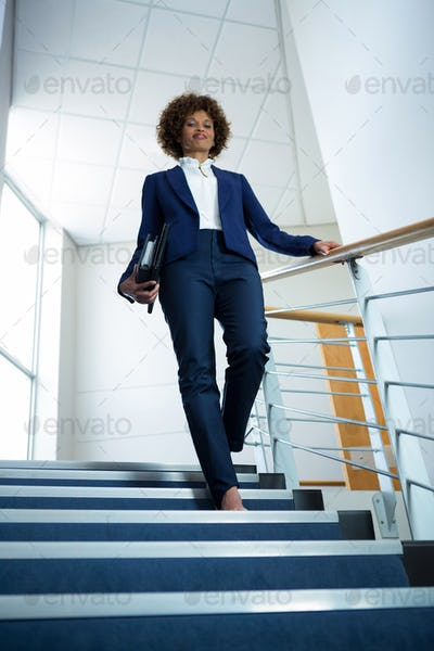 Businesswoman with diary climbing down the stairs